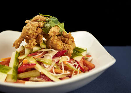 A high angle shot of a delicious crispy fried chicken salad in a white plate