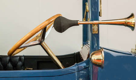 The front of a vintage blue car with an antique golden steering wheel and a separate horn Imagens