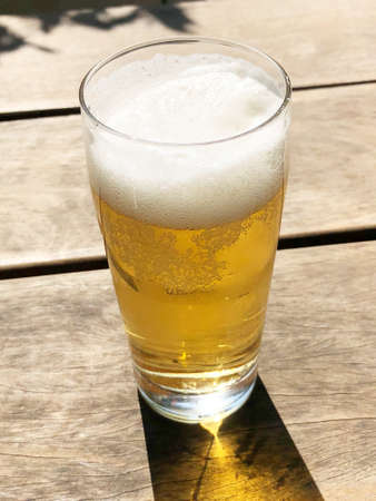 A vertical shot of a glass of cold beer on a wooden surface Standard-Bild