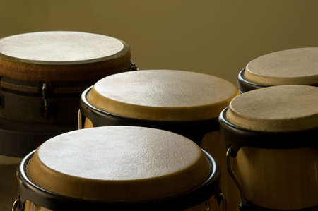 A closeup of bongo drums under the lights against a yellow background