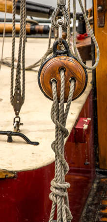 A vertical shot of a wooden pully with ropes attached