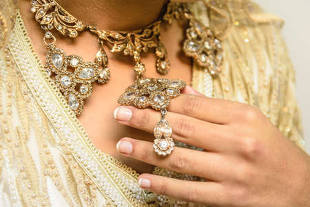 A closeup shot of a female wearing a necklace with precious stones