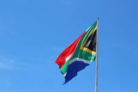 A low angle shot of the South African flag in the wind under the clear blue sky