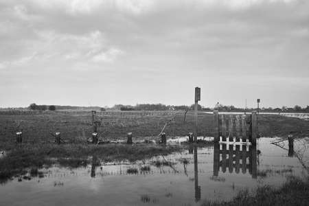 A greyscale shot of a small fence reflected in the lake in a valley in a rural area Banque d'images