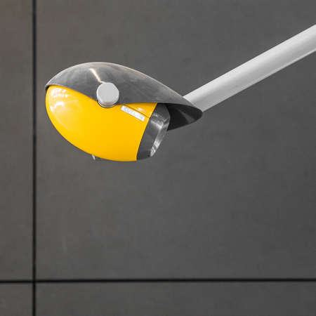 A closeup shot of a yellow and black lamp attached to a wall