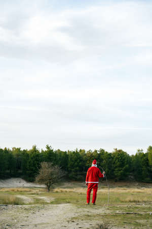A vertical shot of lonely Santa Claus walking in a grassy field with a stick in his hands