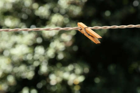 A selective focus shot of a wooden clothespin on a wire with a blurred natural background Standard-Bild