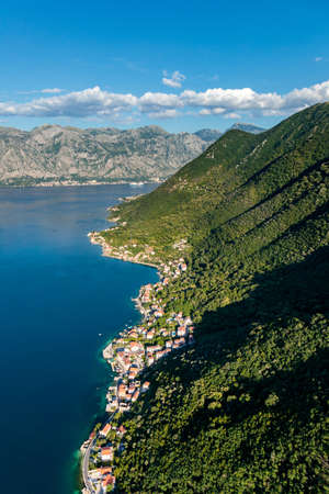 A vertical shot of buildings near the forested mountains and the sea in Kotor, Montenegro