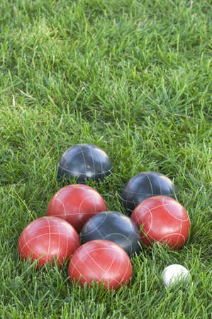 A vertical picture f colourful bocce balls on the lawn under the sunlight