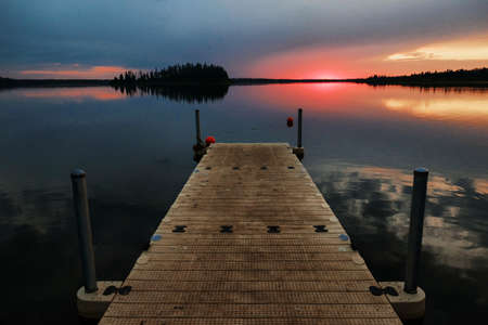 A high angle shot of a wooden pier in the water during the sunset