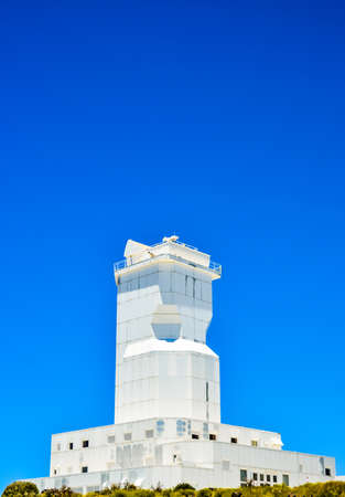 A low angle shot of a modern architectural white building of canary islands in spain with a clear blue sky in the background