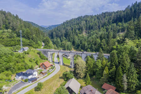 An aerial shot of the Stoparjev bridge in Slovenia surrounded by trees and mountains