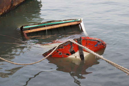 A high angle shot of a broken sinking sailboat in a river