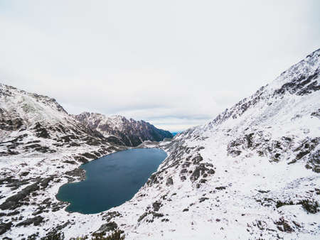 A beautiful scenery of a lake surrounded by the Tatra Mountains covered with snow in Poland Фото со стока