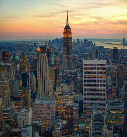 A high angle shot of city buildings in new york manhattan with a sunrise in the background