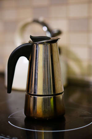 A vertical closeup shot of a metallic kettle placed on the electric stove with a blurred background Standard-Bild