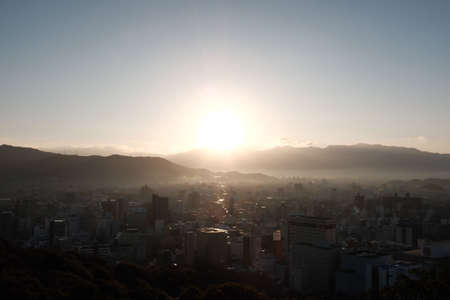 A city surrounded by hills covered in greenery under a blue sky during the sunset