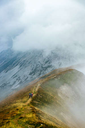 Hikers going up a mountain trail in the styrian mountains in austria, hiking trail, sport, misty mountain early in the morning, ascending