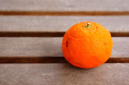 A closeup shot of a fresh tangerine on a wooden surface