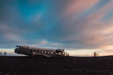 The Abandoned DC plane on Solheimasandur surrounded by people under a cloudy sky during the sunset
