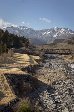 On the outskirts of Nikko, Japan lies a dried riverbed with a beautiful snowy mountain in the background.