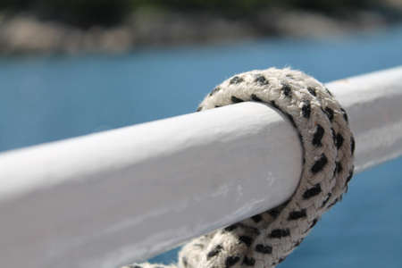 A closeup shot of a black and white rope tied in a metal handle with a blurred background