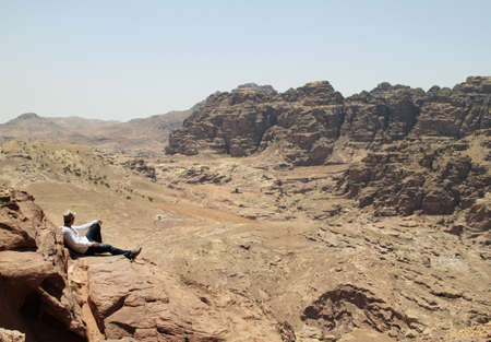 A man sitting around the famous archeological site Petra in Jordan under the sun