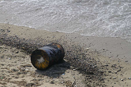 A large metal container tossed on the sand of the beach