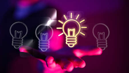 A businessman working with a virtual projection of digital creative idea lamps - business success concept