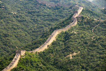 A high angle shot of the famous Great Wall of China surrounded by green trees in summer