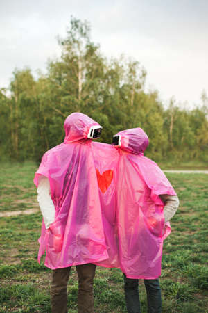 A vertical shot of two people looking at each other in VR headsets sharing a pink plastic raincoat