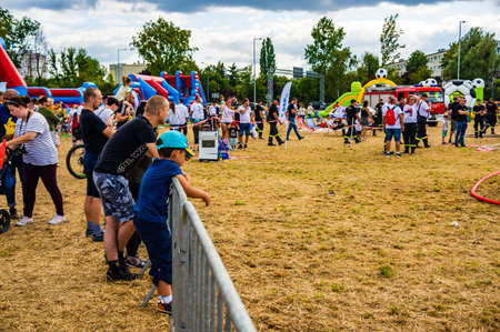 POZNAN, POLAND - Aug 03, 2019: People standing by a metal fence looking at a show during a fire department event.