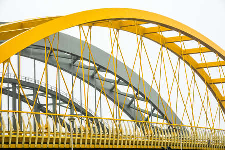 A modern bridge with yellow and grey fragments on a white background