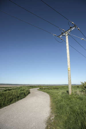 A bottom view shot of a transmission line in a grassy field next to a narrow road