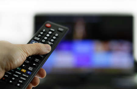 A person holding a black remote control in front of the TV Banco de Imagens