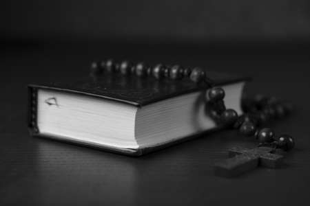 A greyscale shot of the Bible with a cross necklace over the book 版權商用圖片