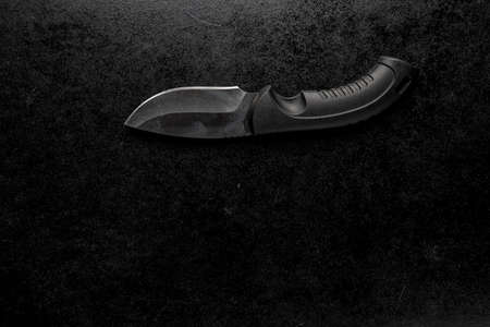 A black sharp small knife with black handle