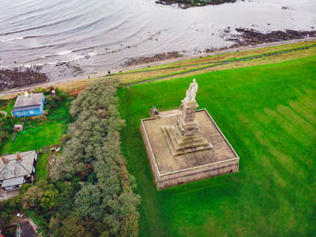 An aerial shot of a statue in the green valley near the sea