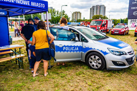 POZNAN, POLAND - Aug 03, 2020: Women and kids standing by a exposition police car with open doors during a fire department event. Kids sitting inside the vehicle.