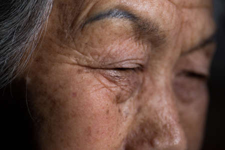 A closeup shot of the wrinkled face of an elderly Chinese female