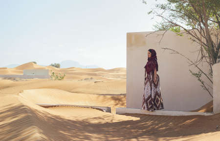 A female walking in the desert through the abandoned town of Al Madam, UAE