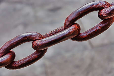 A closeup shot of a brown iron chain with a blurred grey background Imagens