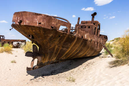 An isolated wrecked and rusted ship on the sand in Muynak Uzbekistan