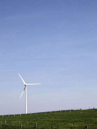 A vertical shot of a grassy field with a windmill in the distance under a blue sky