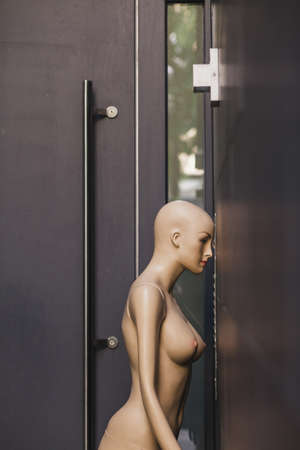 A vertical shot of a naked female mannequin near a black wall