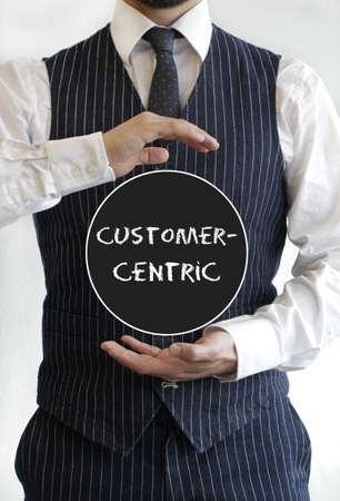 A man with a customer-centric text written on a black circle in the middle of his hands