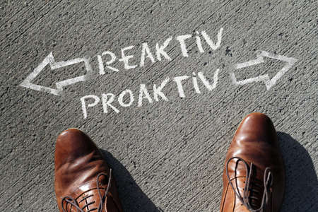 A high angle shot of reactive and proactive marked with opposite directions on the ground
