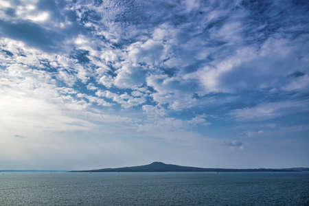 A beautiful shot of the Rangitoto island under a blue cloudy sky in Auckland, New Zeland