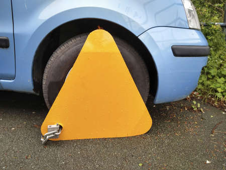 Untaxed car illegally parked in public place with wheel clamp in the UK Foto de archivo