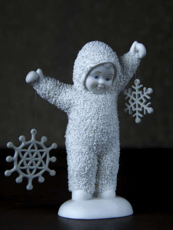 A vertical shot of a cute baby statue holding snowflakes